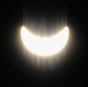 Die Sonne mit Mond und Schlieren auf der Linse
